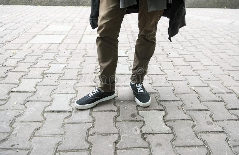 Legs in narrow  black sneakers stock photos