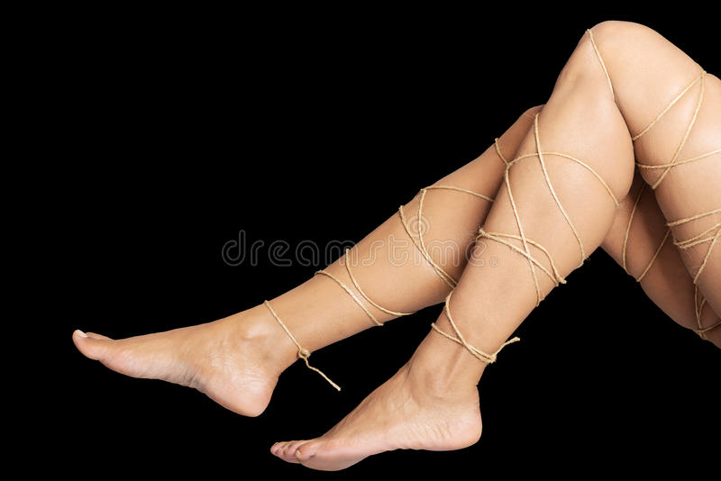 Legs pain concept - legs tied with rope. Isolated stock photography