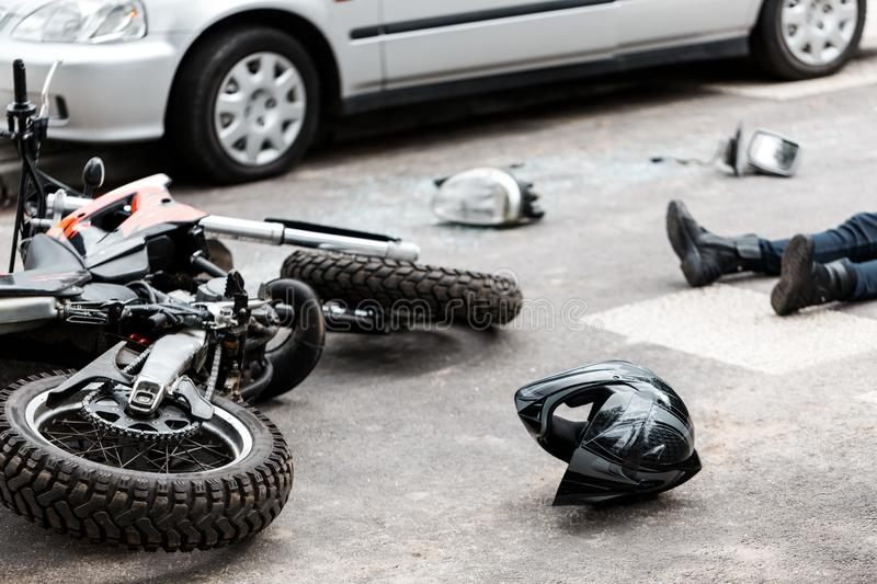 Motorcycle and car accident. Legs of a person lying on the road after a motorcycle and car accident royalty free stock photos