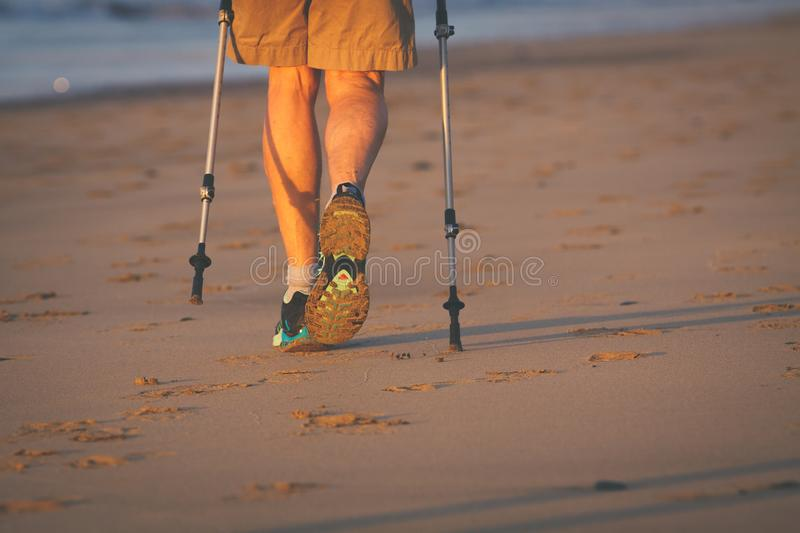 Legs and poles of nordic walker old woman. On the beach stock image