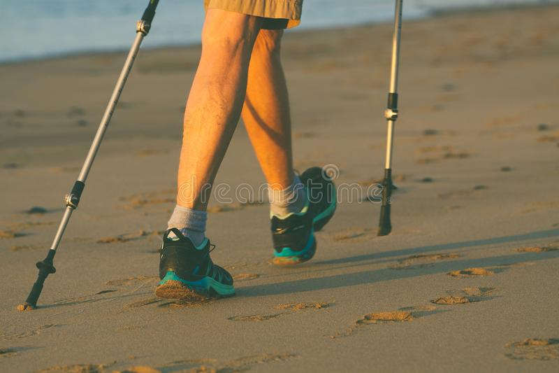 Legs and poles of nordic walker old woman. On the beach royalty free stock photography