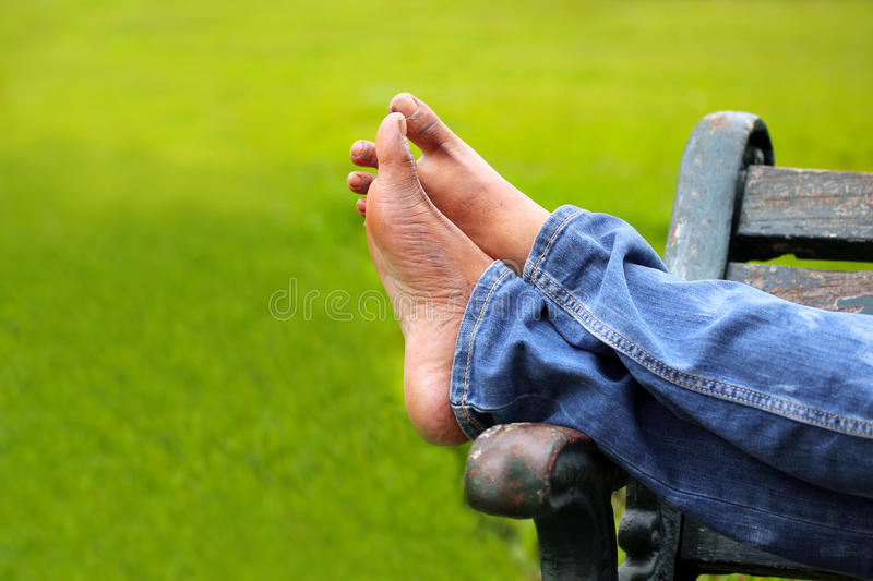 Legs of relaxing adult person on a park bench stock photo