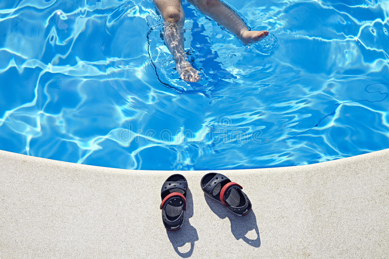 Legs and Sandals at the swimming pool. At sunny day. Copy space royalty free stock photography