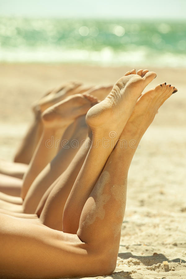 Legs of several girls. Lying on sandy beach and tanning in the bright summer sun stock images