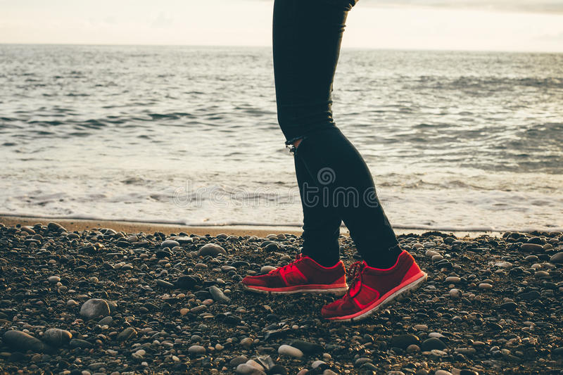 Legs and sneakers on the sea beach. stock photos