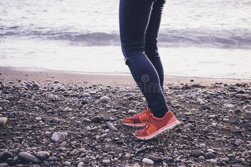Legs and sneakers on the sea beach. stock images