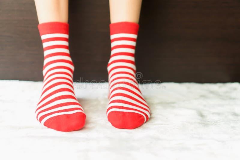 Legs in socks red colors alternate, white side stand on white fabric floor. Legs in socks red colors alternate, white side stand on white fabric floor stock photography