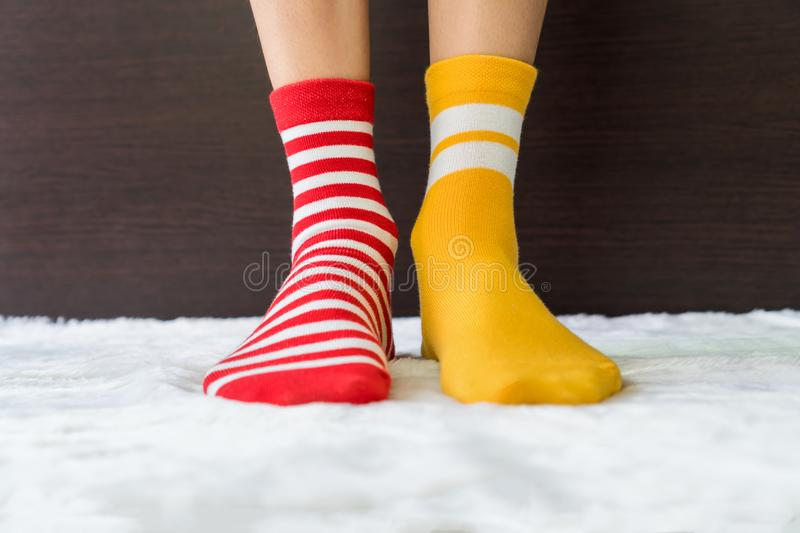 Legs in socks two colors alternate, Red and yellow side stand on white fabric floor. Legs in socks two colors alternate, Red and yellow side stand on white stock image