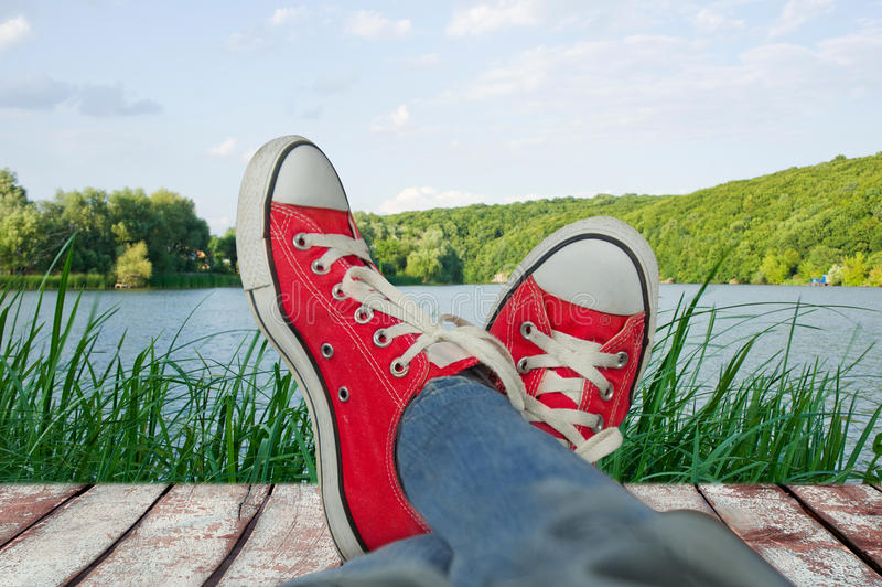 Legs in sport shoes on holiday, with a view of nature.  stock image