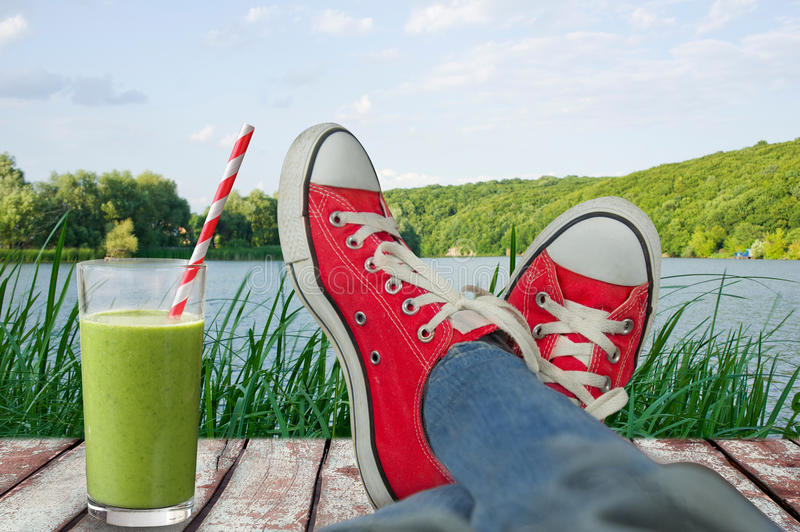 Legs in sport shoes on holiday, with a view of nature and a cold. Juice royalty free stock images