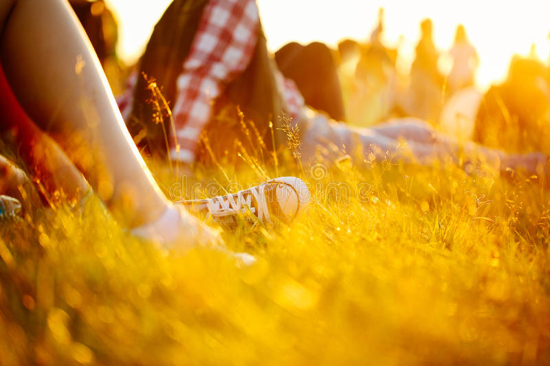 Legs in sport shoes or sneakers in grass. summer lifestyle. Colorful warm yellow toning. People on holiday laying on ground. recre. Ation in park nature. Music stock image