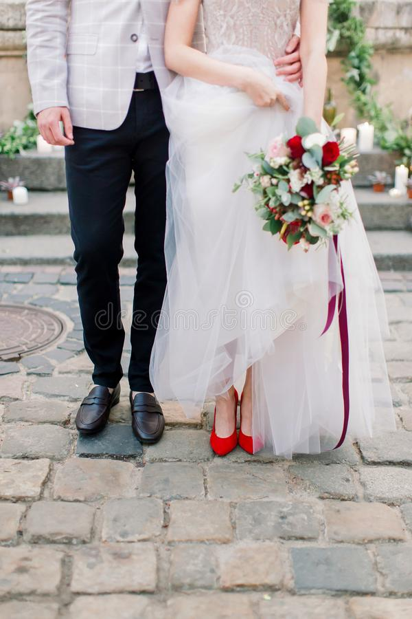 Legs of the stylish wedding couple, groom in black shoes and bride in red heels shoes with a luxury wedding dress stock photography