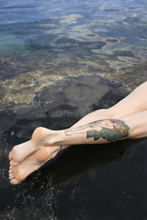 Legs of tattooed woman.