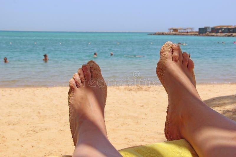 Legs of girl sunbathing under sunshade. Enjoying summer vacations stock photo