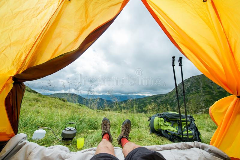 Legs of the traveler in hiking boots in a tent outdoors.  royalty free stock photography