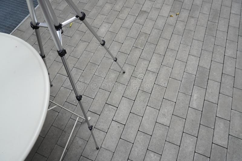 The legs of the tripod for the phone or camera are on the asphalt. the equipment of the photographer, used to shooting video or royalty free stock photography