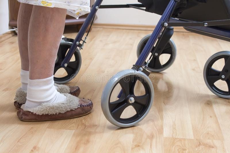 Legs of a very old woman in white socks and slippers. The old lady learns to walk with the help of a rehabilitation walker. royalty free stock photography