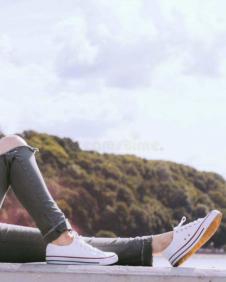 Legs wearing trousers and sneakers. Trendy fashionable unrecognizable woman relaxing outdoor wearing casual footwear white sneakers and hole trousers stock images