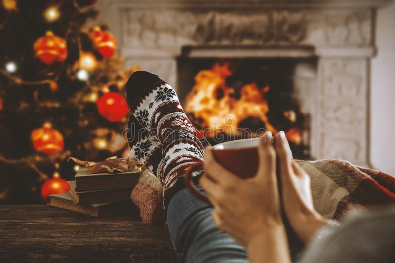 Wooden table with legs in christmas socks, a mug in woman`s handsand, space for your decoration, products and text. Legs in winter christmas socks on wooden top stock photos