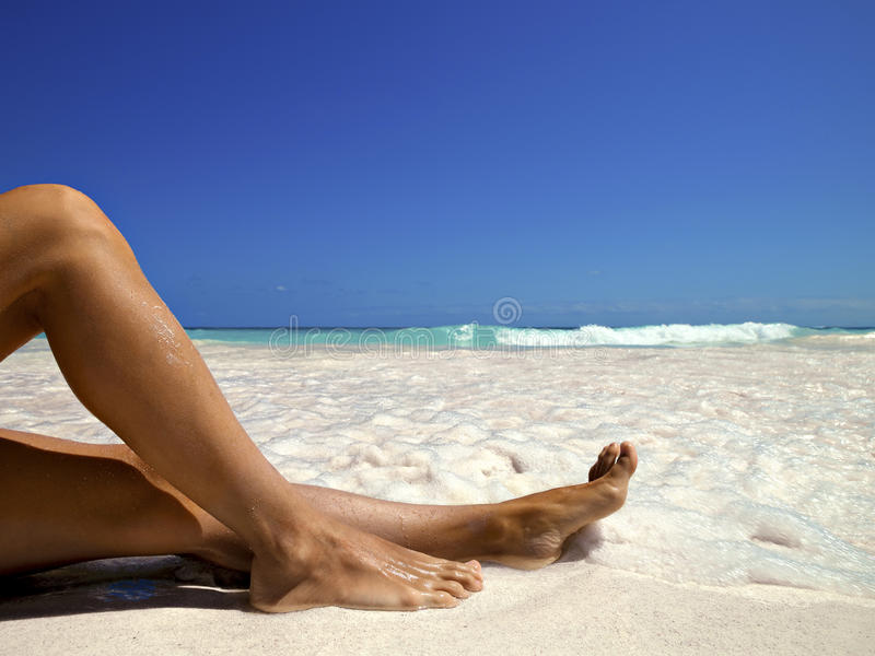 Legs of a woman on the beach royalty free stock image