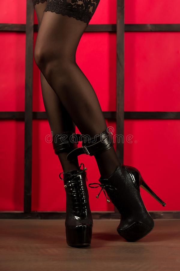 Legs of a woman in fetish wear: stockings, handcuffs and high heels boots with extrem platform stock photo