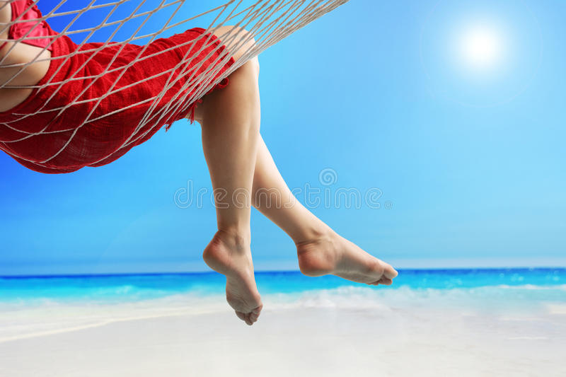 Legs of a woman lying in a hammock by the sea. Close-up on the legs of a woman lying in a hammock on a beach by the open sea royalty free stock photos