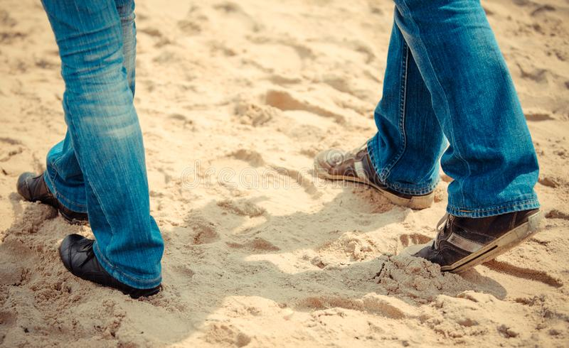 Legs of woman and man on sand at beach. Summer and vacation concept royalty free stock photo