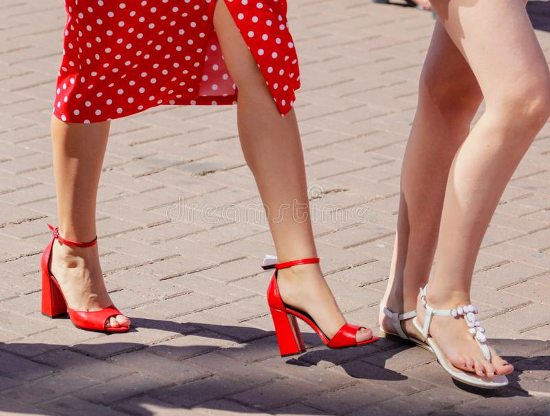 The legs of a woman in red sandals.  royalty free stock image