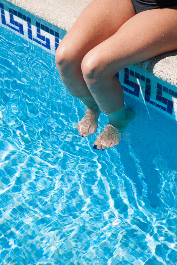 Legs of woman sitting on curb pool royalty free stock image