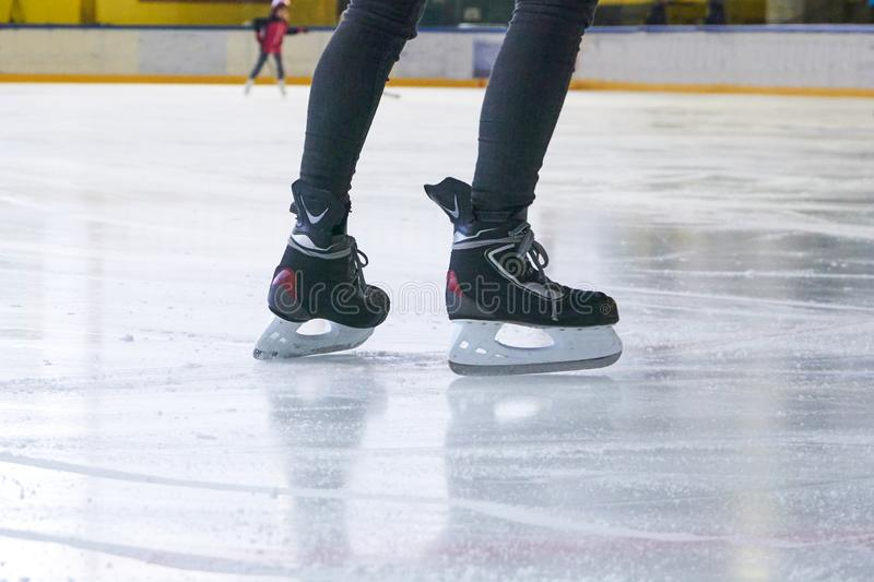 Legs of a woman skating on an ice rink. With Hockey skates royalty free stock images