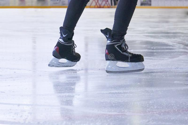 Legs of a woman skating on an ice rink. With Hockey skates royalty free stock photo