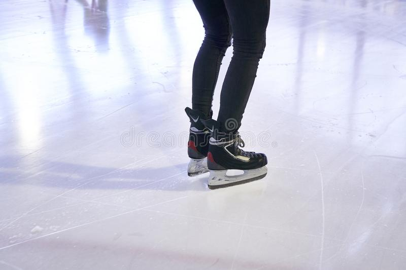 Legs of a woman skating on an ice rink. With Hockey skates stock images