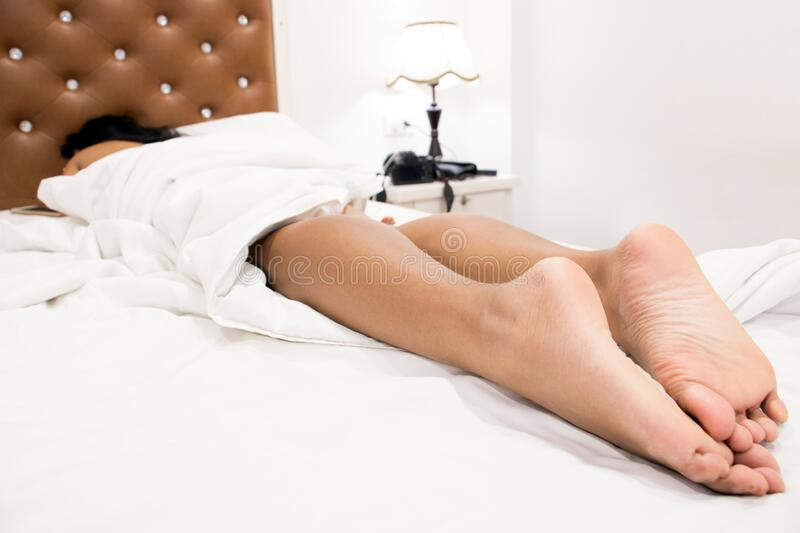 The legs of woman sleeping in bed. stock photo