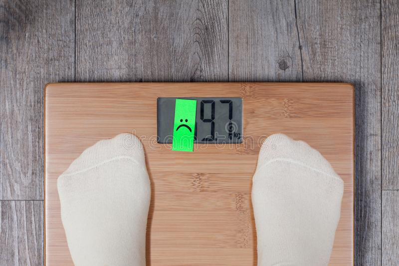 Funny weight concept. Legs of woman standing on weight scale and number on the display is covered with a sticker. Funny weight concept stock photos