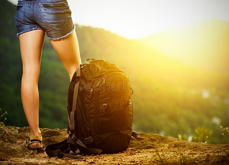Legs of a woman tourist and travel backpack on a mountain top royalty free stock photos