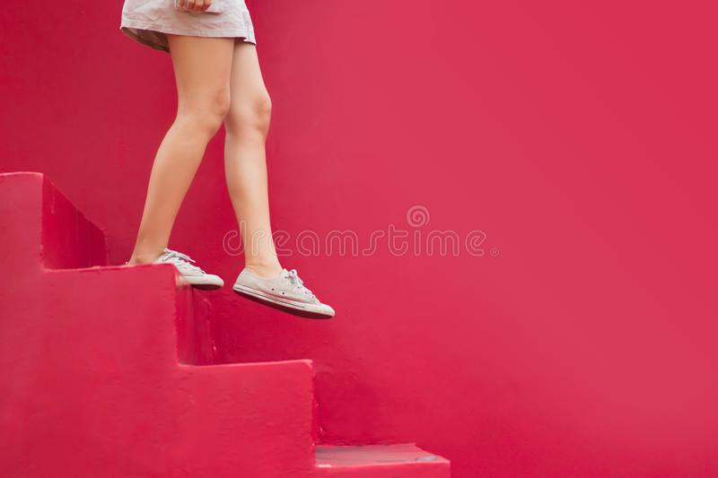 Legs of woman walking down red stair with copy space stock image