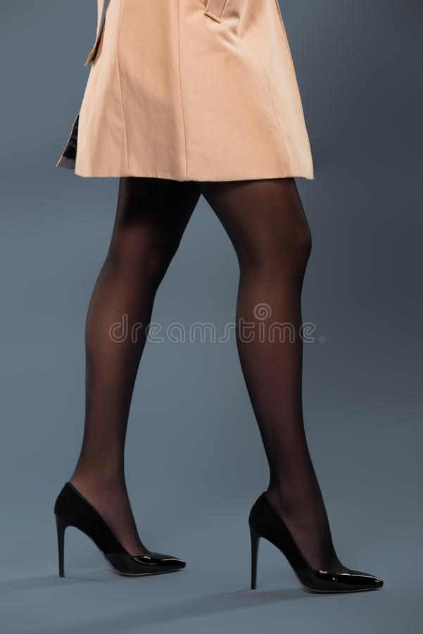 Legs of woman wearing black pantyhose and beige trench stock photos