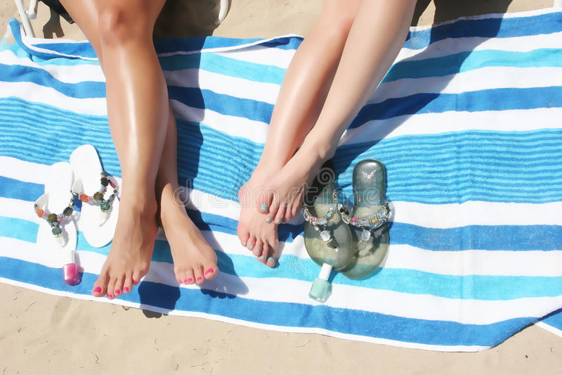 Legs of women on beach royalty free stock image