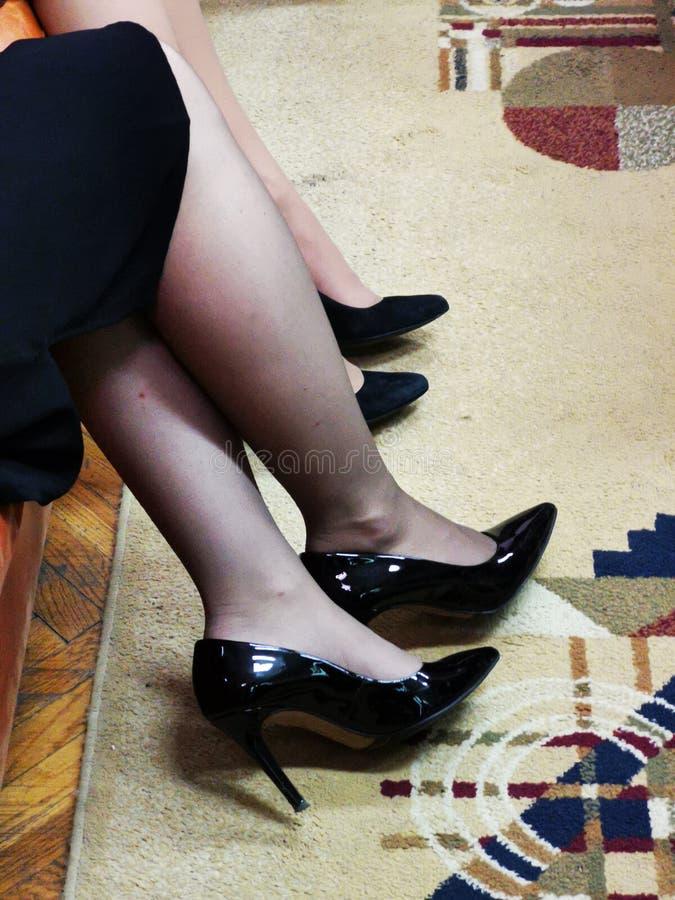 Legs of women - black heels stock photography