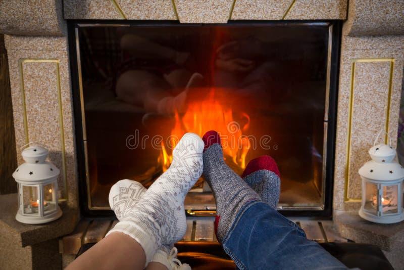 Legs in woolen socks heat up near fireplace stock images