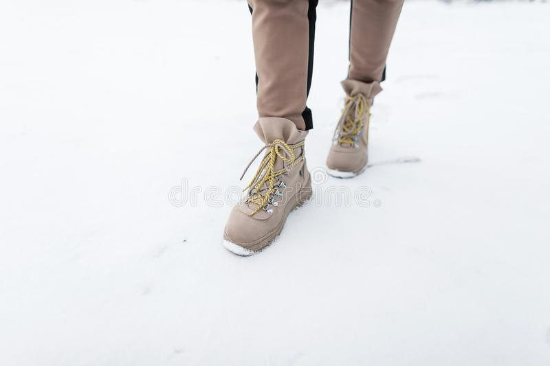 Legs of a young girl in trendy pants with brown winter boots walk on snow. Winter collection of fashionable shoes. Close-up. stock photography