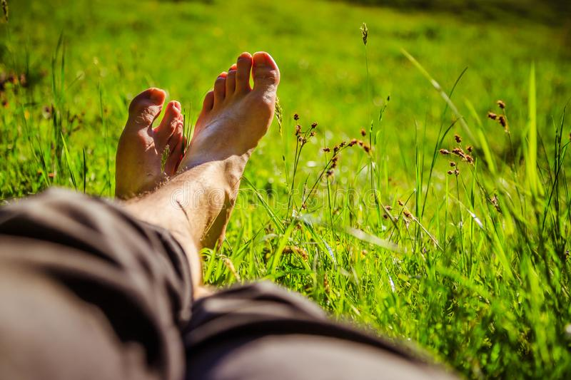 Chilling in the green grass: Legs of a young man, relaxing, summertime. Legs of a young man in the green summer grass, summertime relaxing chill happiness royalty free stock photo