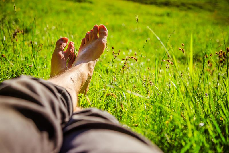 Chilling in the green grass: Legs of a young man, relaxing, summertime. Legs of a young man in the green summer grass, summertime relaxing chill happiness stock photos