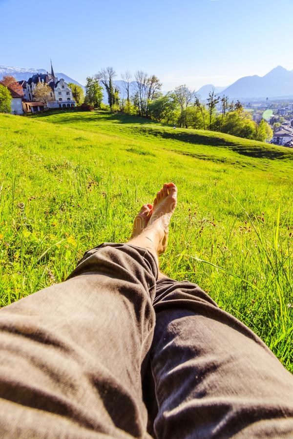 Chilling in the green grass: Legs of a young man, relaxing, summertime. Legs of a young man in the green summer grass, summertime relaxing chill happiness stock image