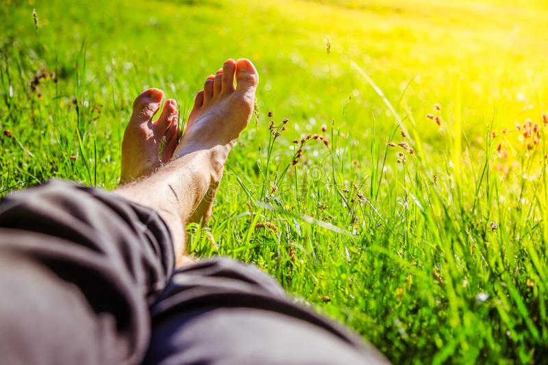 Chilling in the green grass: Legs of a young man, relaxing, summertime. Legs of a young man in the green summer grass, summertime relaxing chill happiness royalty free stock images