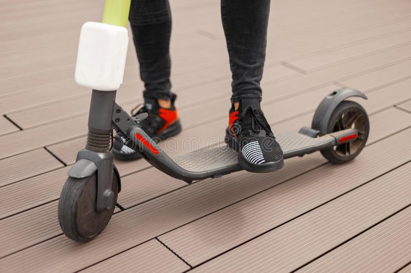 Legs of a young man in a stylish jeans outfit are standing on an electric scooter on a wooden floor. Fashionable guy. Resting after riding a modern scooter stock photography