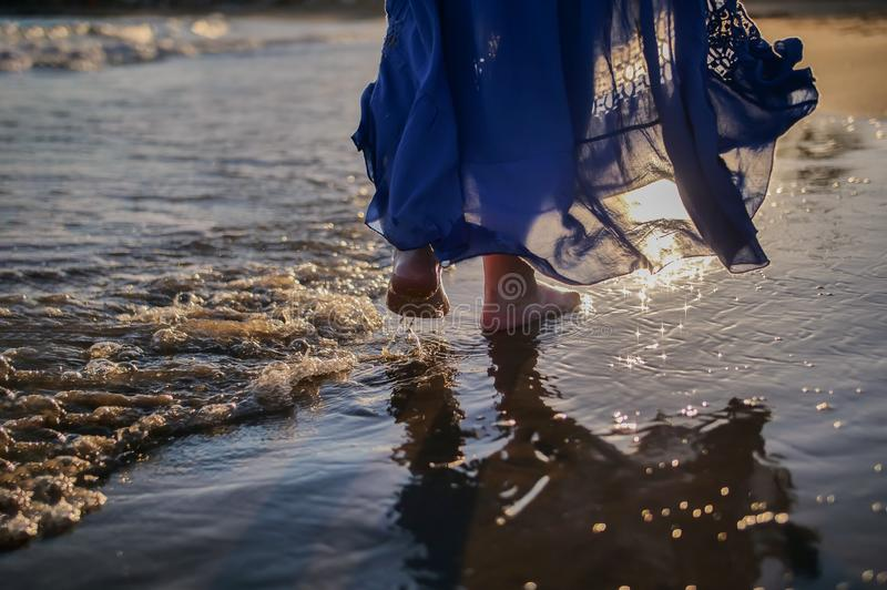 Legs of a young woman in a blue long skirt walks along the beach, the sun glare on the waves, sunset stock photo