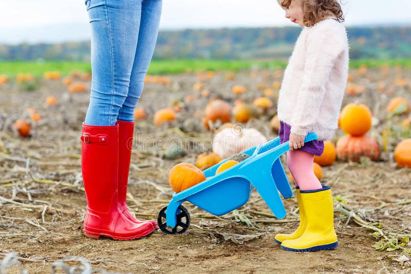 Legs of young woman and her little girl daugher in rainboots. stock photos