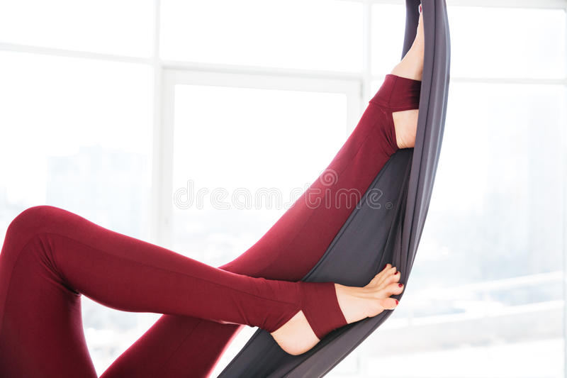 Legs of young woman in leggins using hammock at studio. Closeup of beautiful legs of young woman in leggins using hammock in studio royalty free stock images