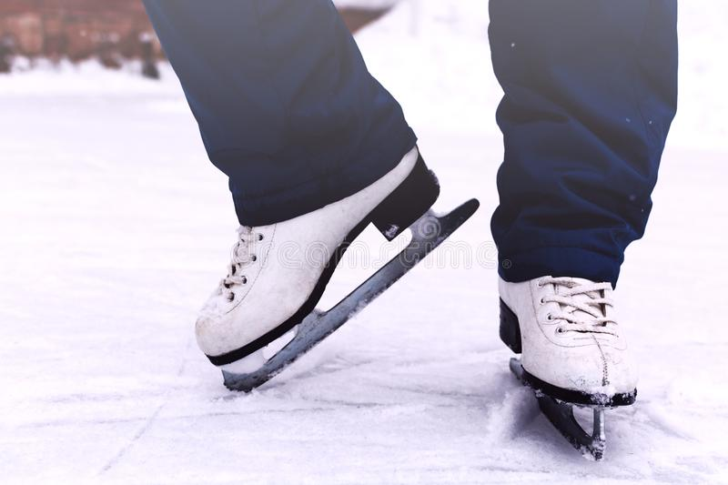 Legs of a young woman skating on the winter rink stock images